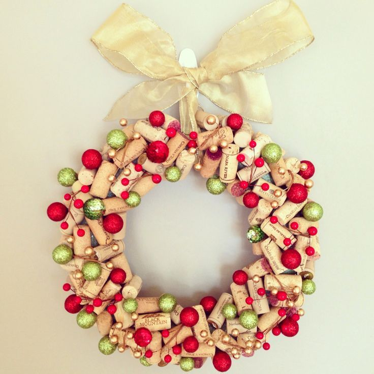 "Wine cork Christmas wreath, made using: 12 inch foam wreath, leftover wine corks, two strands of faux decorative holly, mini Christmas ""fillers"" (found at Michael's), and a hot glue gun. Glue corks to f"