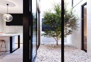 Bastano dei ciottoli bianchi, richiamati dalle pareti in mattoni ridipinti, e un albero per creare un lucernario poetico, oltre che funzionale. Il living di Fairbairn House trae luce naturale durante l'orario diurno, dimezzando i consumi