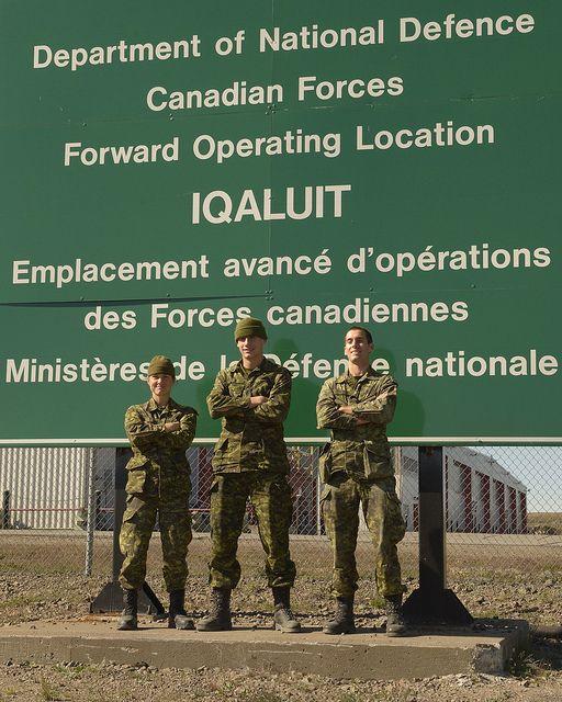 De gauche à droite : le sergent Geneviève Côté, le soldat Étienne Duchesne et le soldat Tommy Dostie, membres du Groupe-compagnie d'intervention dans l'Arctique du 35e Groupe-brigade du Canada, posent devant une affiche des Forces armées canadiennes pendant l'opération Nanook 2013 le 18 août 2013.