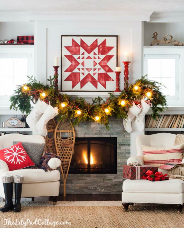 Cozy ski lodge Christmas Mantel Decor featuring a red and white quilt sign, snow shoes and fresh garland.