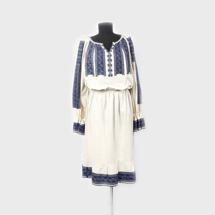 Romanian blouse from Muscel  Cămaşă femeiască cu poale, bogat decorată cu albastru și auriu, de Muscel. Sfârșitul sec. XX  Piesa este o interpretare modernă de vestimentaţie feminină - rochie - obţinută prin transferul broderiei tradiţionale de la o ie de Muscel interbelică.