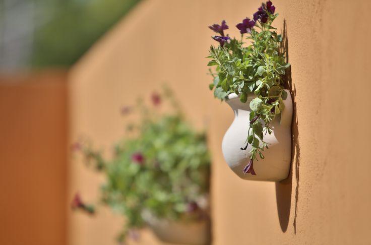 Decora la pared de tu jardín con macetas para da un toque diferente.