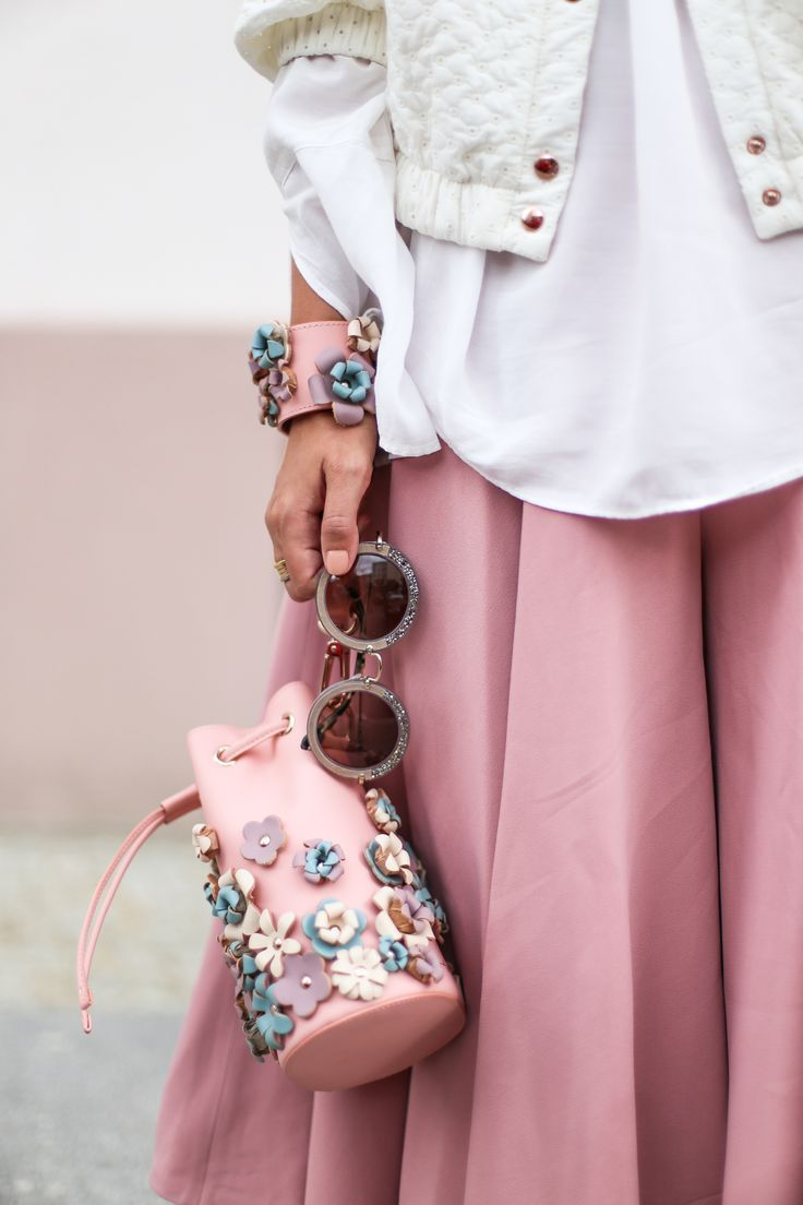 A little Clueless. Pink skirt, pink clutch with flowers, rounded sunglasses and white shirt.