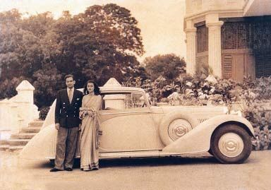 Maharani Gayatri Devi of Jaipur poses next to a custom built Rolls-Royce motor car.