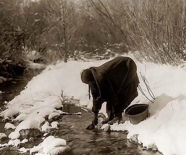 Above we show a vital Indian photo of a woman getting watter. It was made in 1908 by Edward S. Curtis.    The illustration documents a Crow (Apsaroke) woman standing in the snow scooping up water from a a small stream with a can. She has another bucket beside her.    We have compiled this collection of artwork mainly to serve as a vital educational resource. Contact curator@old-picture.com.