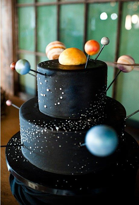 "How cool is this astronomy-themed groom's cake shot by Laurel McConnell?! According to the couple's wedding planner Holly-Kate Foss of Holly-Kate & Company, the bride secretly had the cake made as a surprise for her groom, an astronomy buff who loves debating the existence of a possible ""new"" planet nicknamed Tyche. Kaysie Lackey, owner of The People's Cake in Seattle, covered the two tiers in black fondant and dusted them with stars; she also hand-painted each planet and designed a custom…"