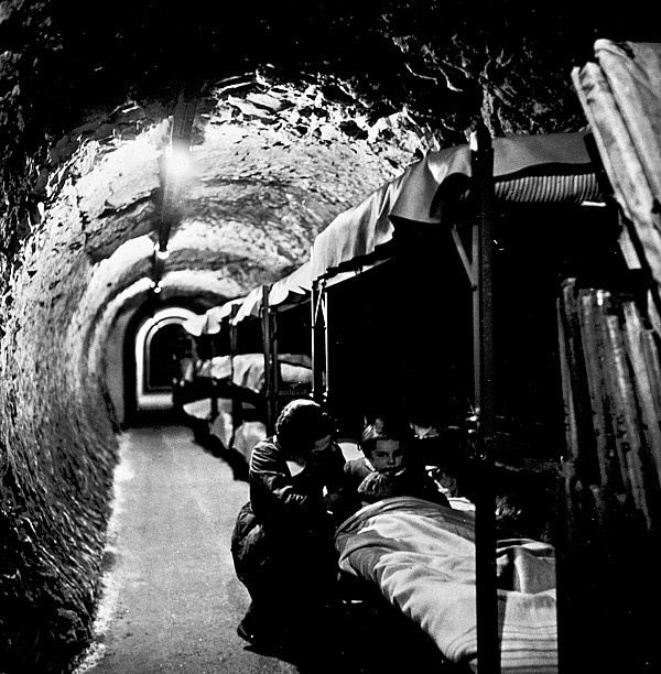 WORLD WAR II: BOMB SHELTER. A woman kneeling beside a girl in a bunk bed in a bomb shelter located in a subway tunnel beneath London, England, 1940-45, during World War II. Photographed by Tony Frissell.