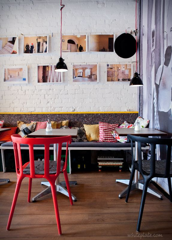 photo wall, red chair, collected pillows hanging pendant light.
