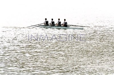 Four teenage boys rowing crew in boat, b photo