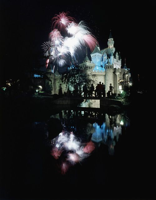 July 17, 1955: Disneyland opens  Pictured: Night view of Disneyland and the Sleeping Beauty's castle with fireworks exploding over it, people watching silhouetted against light.