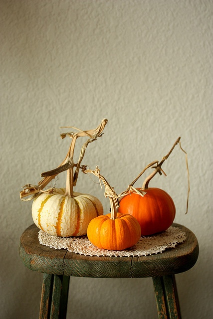Pumpkins displayed on a vintage wooden stool!!! Bebe'!!! This illustrates the importance of having decorations at various heights and eye levels whether sitting or standing!!!