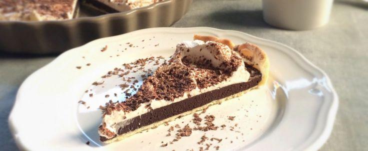 Crostata di frolla ripiena di mousse di cioccolato fondente, coperta di panna montata e decorata con cacao in polvere.