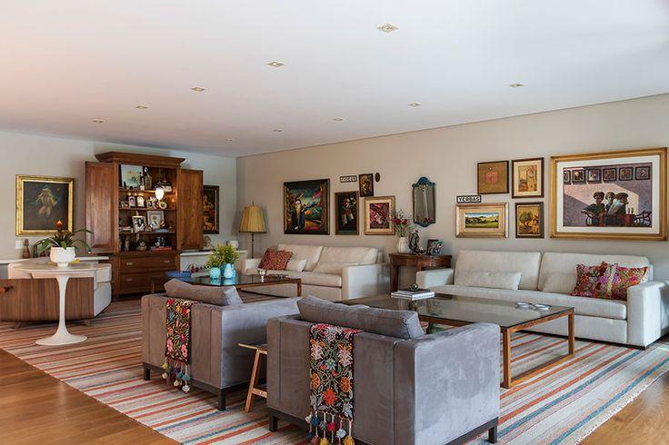 Decoração com personalidade, decoração colorida de sala de estar com obras de arte, almofada estampada, mesa lateral, tapete, sofá cinza, manta colorida, plantas e sofá branco.