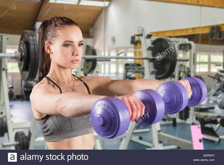 Download this stock image: Woman working with a dumbbell on a background of simulators - G2RNF3 from Alamy's library of millions of high resolution stock photos, illustrations and vectors.