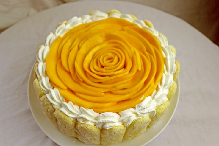 Mango Mousse Cake is just bursting with Mango flavor! So light and delicate! Whipped Cream icing and hand made lady fingers sponge cake. Step by step video
