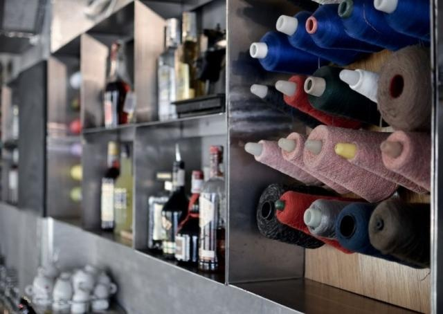 Spools of yarn behind the bar at Papiota Cafe in Romania
