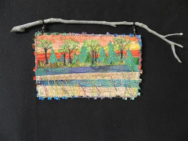 """Riverside.  Small art quilt hanging from a tree branch. Trees are """"drawn"""" using free motion stitching."""