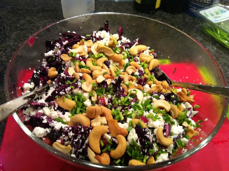 Rode kool salade met cashewnoten, feta en appel. Ingrediënten: gebakken ui, appelblokjes, koriander, rode kool, feta, cashewnoten, rozijnen, appelsap, rode wijn azijn, honing, kruidnagel, bieslook, peper en zout. Eet smakelijk!