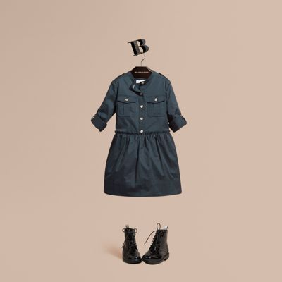 A Burberry shirt dress in comfortable stretch cotton detailed with polished gold-tone buttons. Military-inspired epaulettes and box-pleat pockets accent soft ruching at the waist.