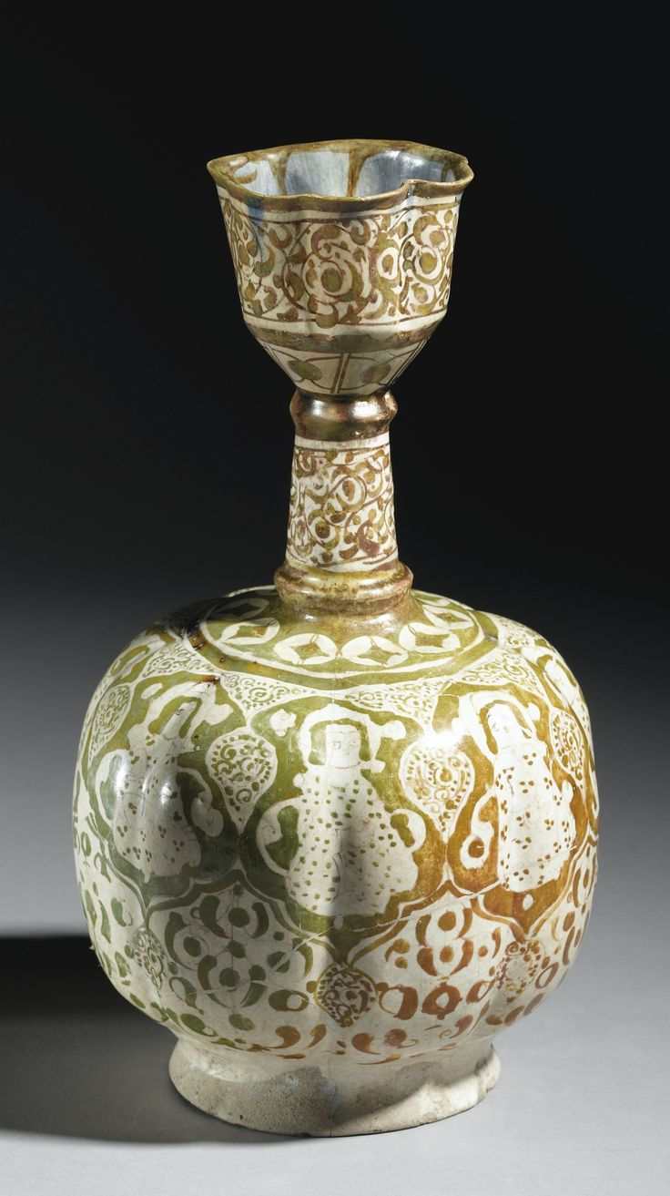 A LARGE KASHAN LUSTRE BOTTLE VASE, PERSIA, 12TH CENTURY the body of ribbed oval from with a tall thin neck and tulip form mouth, the body decorated with a golden overglaze lustre, featuring seated figures within palmette frames, surrounded by scrolling foliate designs, the interior of mouth with a cobalt blue glaze 36.5cm. height.