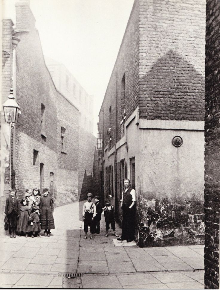 """White Hind Alley, Bankside, Southwark, London, 1896.  The area of London which now includes the Tate Modern, Bankside is literally that - on the banks of the Thames.  Two of the children on the right in this photograph are shoe-less, the pavement is so uneven that the council would probably have been sued by now these days.  In """"Ragged London in 1861"""", by John Hollingshead, the author writes:  """"In White Hind Alley, near this place, there is a row of old black, rotten, wooden dwell"""
