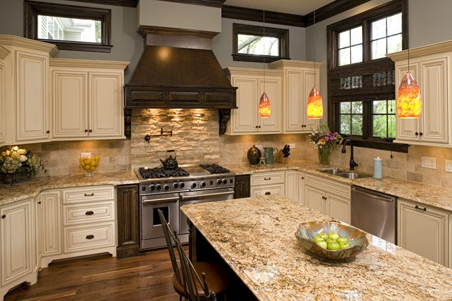 Antique glazed cabinets, travertine backsplash, with gray walls and black countertops