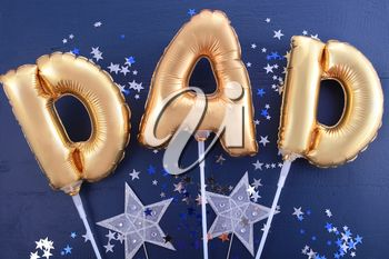 Happy Fathers Day gold baloons for the word, Dad, on dark blue wood background with silver and blue scattered glitter stars.