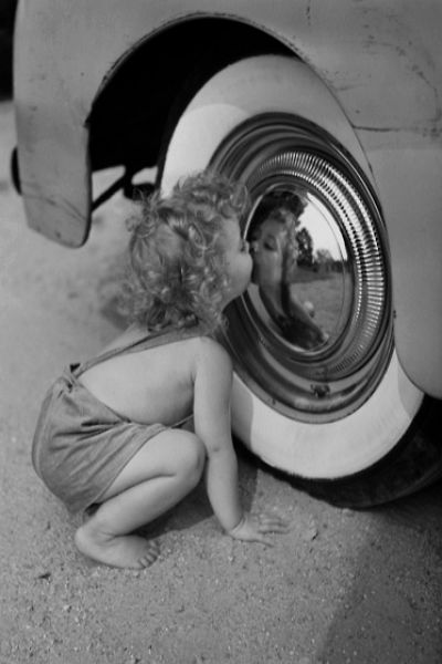 Girl looking at her reflection in hubcap - by Constance Bannister