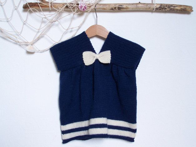 Robe tricotée en jersey coloris bleu-marine et rayures écru.Taille 6 mois. Epaules réalisées au crochet en mailles serrées.  Petit noeud au crochet coloris écru. Laine 65% mérinos, 35%...