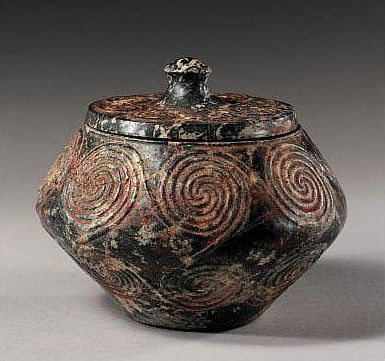 A Minoan Serpentine Pyxis and Cover, Middle Minoan I, 2160-1700 B.C., of biconical form, with flat base, slightly everted rim, and knobbed lid, the exterior carved in shallow relief with a linked spiral design. Width 4 1/8 in. (10.5cm.); height 3 5/8 in. (9.2cm.)