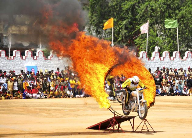 An Indian army soldier performs a stunt on his motorcycle during India's Independence Day celebrations in the southern Indian city of Bangalore August 15, 2014.