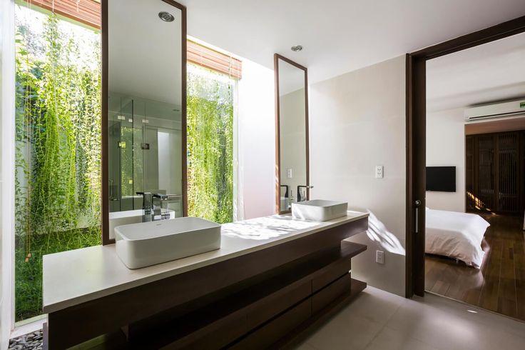 Banheiro da Suite com piso cinza, armário de madeira, tampo banco, espelhos da bancada ao teto com moldura de madeira, vista para o jardim com cortina verde de plantas. Casa Moderna + Jardim no Vietnã por MIA Design Studio