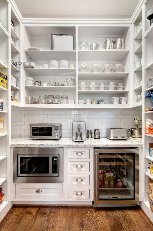 This is a very organized and clean walk-in pantry and kitchen in one. The granite counter top provides space for some kitchen appliances, while underneath are the oven, fridge and drawers. Above are the shelves for dish storage, while high shelves for the food and condiments are on either side.