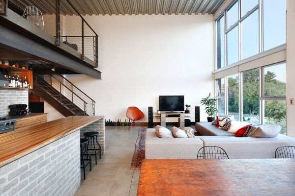 Seattle loft by SHED Architecture & Design – concrete floors, zinc-plated pan-decking ceiling, and blackened steel beams and railings.