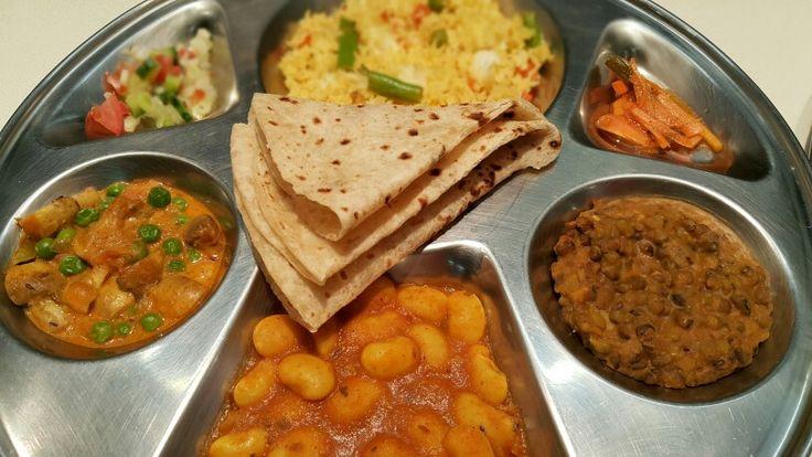 Veg thali: mushrooms and peas; veg rice; salad; pickles; butter beans; mug; roti; papar