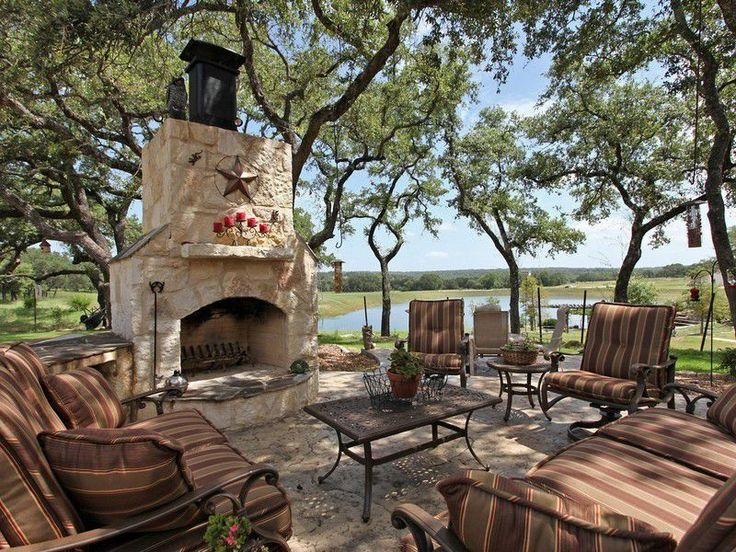 Eclectic Patio with stone fireplace, exterior stone floors, O.w. lee ashbury sofa, outdoor pizza oven, Coffee table