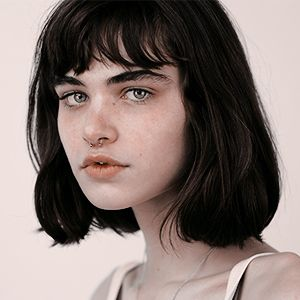 girl short black hair bangs green eyes freckles thick eyebrows