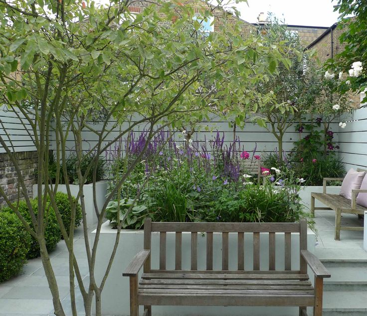The contemporary boundary cladding that is the backdrop for this small city garden is actually recycled wooden decking that has been painted. Design by Ruth Willmott.
