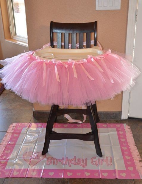 Highchair infused with girl power and pink tulle.  See more first girl birthday party ideas at www.one-stop-party-ideas.com