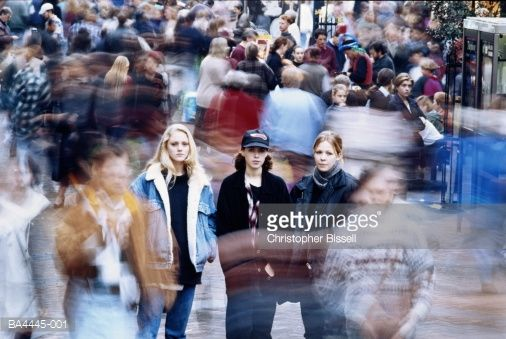 Stock Photo : Three teenage girls (14-16) in moving crowd (blurred motion)