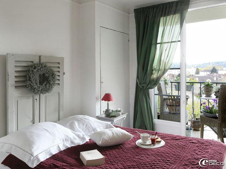 dans une chambre des persiennes d cor es d une couronne v g tale se d tournent en t te de lit. Black Bedroom Furniture Sets. Home Design Ideas