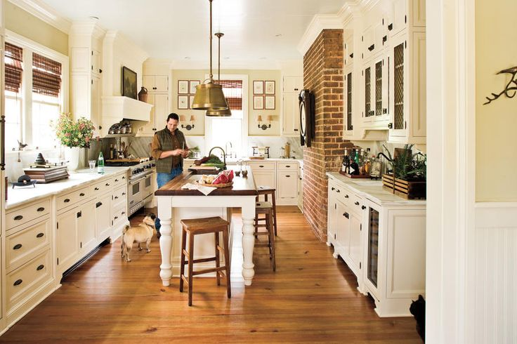 Kitchen - Tour a Restored 19th Century Farmhouse - Southernliving. The kitchen, added in the 1940s, once served as an outdoor hitching station. Jamie updated the room with whitewashed cabinetry, marble countertops, and a generous island.