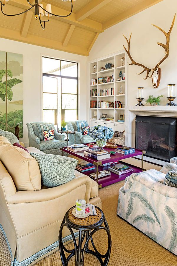 Comforting Colors - 108 Living Room Decorating Ideas - Southernliving. An elk antler trophy is the focal point in this livingroom, andthe palm tree triptych and a blue, green, and mulberry palette create a comfortable environment.