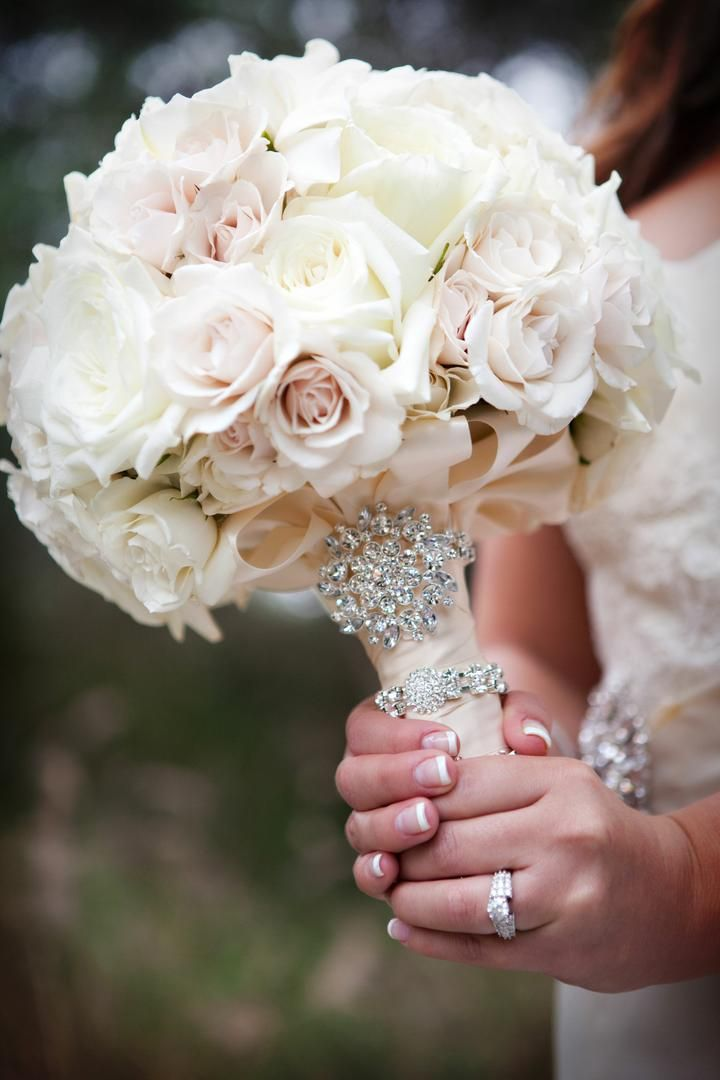 The bride carried a gorgeous bouquet composed of roses in soft pink and ivory hues. The stems were wrapped with a light pink ribbon and fastened with a crystal wrap and brooch. Photography: Darin Fong Photography. Read More: http://www.insideweddings.com/weddings/outdoor-ceremony-purple-and-white-ballroom-reception/372/