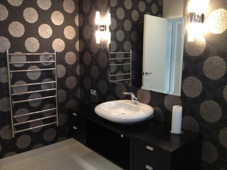 The wallpaper adds sophistication and luxury to this bathroom.