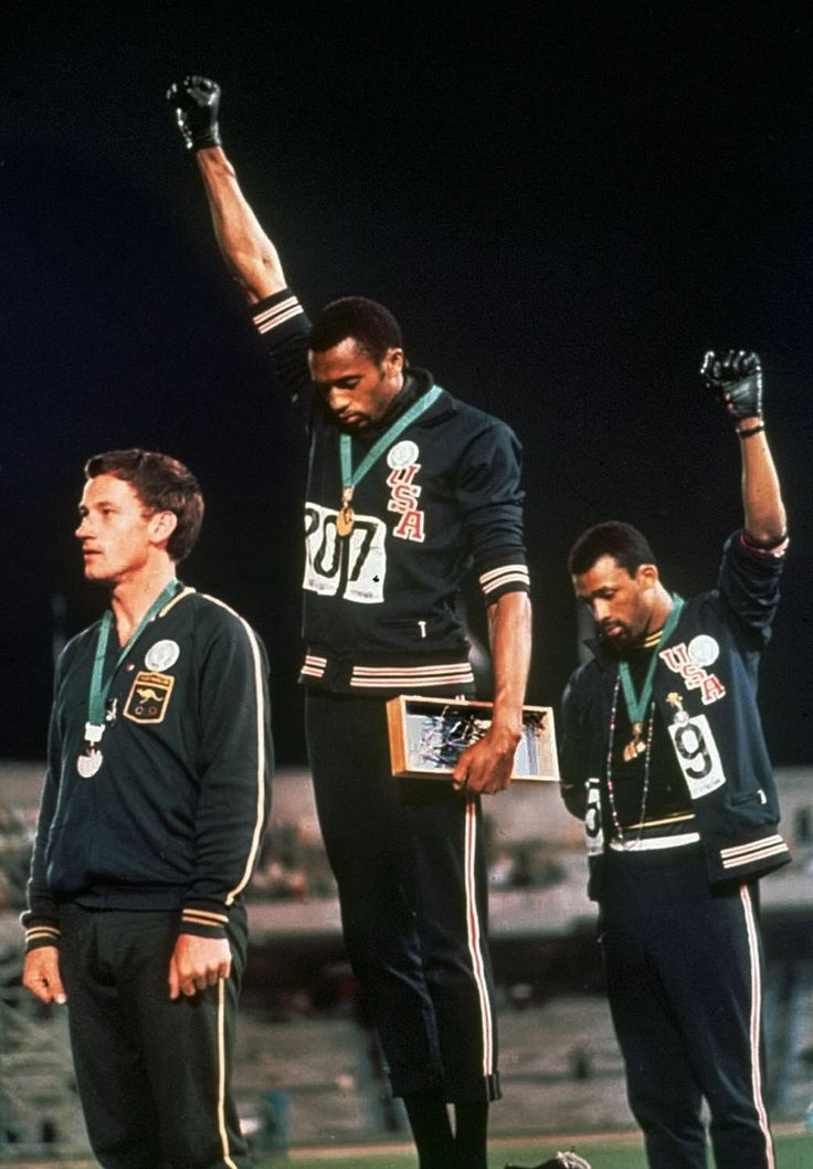 With one glove each Tommie Smith is on the gold medal platform John Carlos is on the bronze raising their fists in a Black Power salute. Silver medalist Peter Norman is wearing a badge in support [2086 3000]