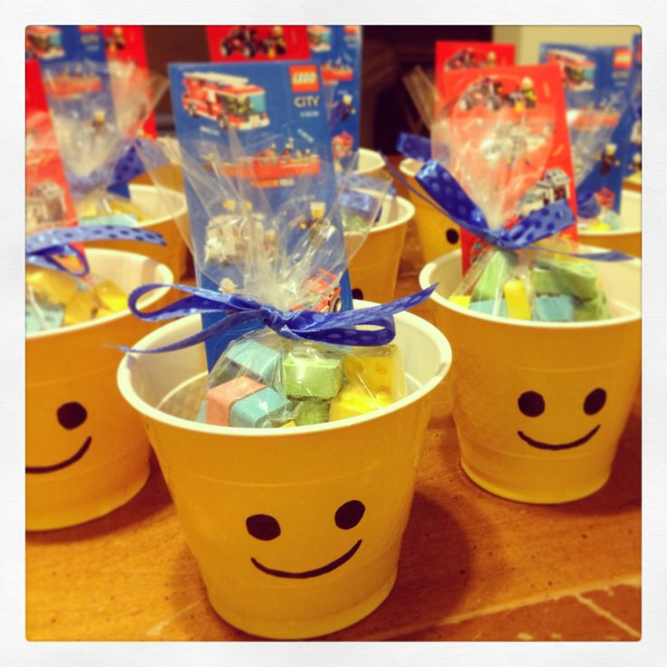 Lego Birthday Treats... Drew Lego face on yellow cups with a permanent marker.  Put 3oz. Lego building blocks candy in cellophane bag tied with ribbon & a sheet of Lego stickers in the cup.  Ta-dah!