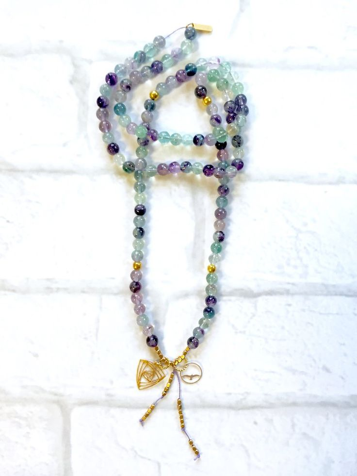 Fluorite  Mala Necklace Intentional jewelry made with fluorite gemstones and sacred geometry pendents. Used during meditation, yoga practice or simply worn as a beautiful piece of jewelry. Each gemstone hold unique healing properties and can be used as a daily reminder of your positive intentions.