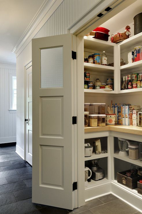 source: Crisp Architects  Lovely kitchen features double doors opening to walk-in pantry lined with horizontal paneling and open cabinets with butcher block countertop over slate tiled floor.