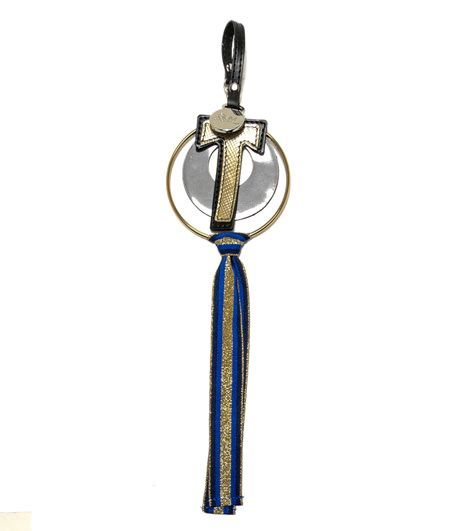 KEY RING WITH LETTER T-Made in Italy keyring with gold tone metal key ring and artificial leather ring and letter T. Striped and Lurex ribbon around the metal ring. Leather strip with a little snap hook. Gum - Gianni Chiarini Design logo plaque. Measurements: length: about 29 cm.